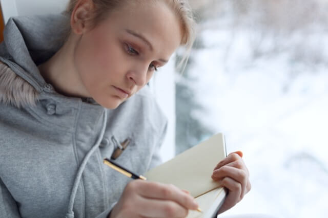 Young girl writing in her journal while sitting at a large window.